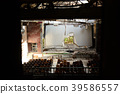 See the broken movie screen in the abandoned theater from the window 39586557