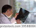 Back turned concentrated radiologist reading X-ray 39588084