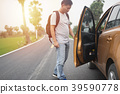 A man is holding a car door on the country road. 39590778