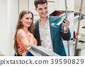 Woman with her man looking at blue shoes in store 39590829