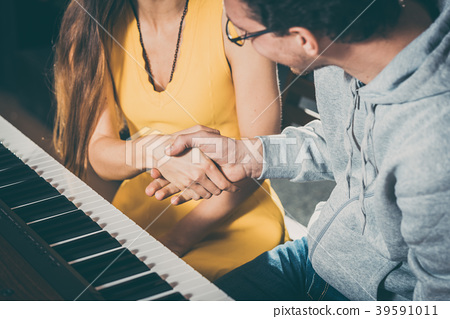 Piano teacher and student shaking hands after