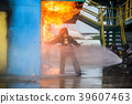 Firemen using water from hose for fire fighting. 39607463