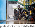 Firemen using water from hose for fire fighting. 39607464