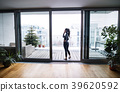 Woman by the window with smartphone, making a 39620592