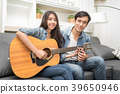 Lover couple resting at home and playing guitar. 39650946