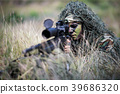 Sniper laying on the grass looking through scope. 39686320