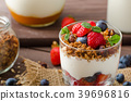 Yogurt with baked granola and berries in small glass 39696816