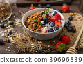 Yogurt with baked granola and berries in small bowl 39696839