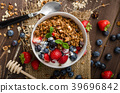 Yogurt with baked granola and berries in small bowl 39696842