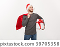 Christmas Concept - Young happy beard man holding 39705358