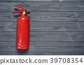 Fire extinguisher on wooden planks 39708354