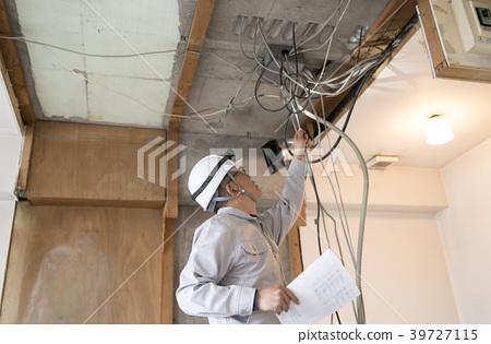 一名工人在持有公寓,骨架翻新,電氣工作和圖紙時進行檢查 39727115