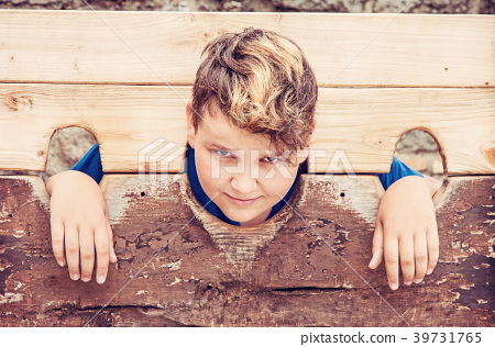 Young caucasian boy in medieval pillory, filter 39731765