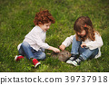 boy and girl playing with rabbit in park 39737918