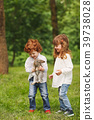 boy and girl playing with rabbit in park 39738028