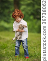 litle boy plays with rabbit in park 39738062