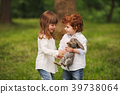 boy and girl playing with rabbit in park 39738064