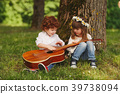 boy and girl playing guitar in summer park 39738094