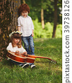 boy and girl playing guitar in summer park 39738126