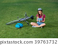 Young girl sitting near bycicle on grass. 39763732