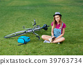 Young girl sitting near bycicle on grass keeping a 39763734
