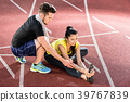 Man and woman on cinder track of sports arena 39767839