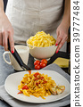 Chef prepares tagliatelle with garlic and cherry tomatoes 39777484