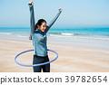 Happy woman with hula hoop on the beach 39782654