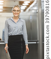 Clever business lady standing near office lift 39790816