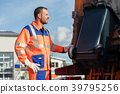 Garbage collection worker putting bin into waste 39795256