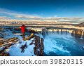 Photoghaper taking a photo at Godafoss waterfall. 39820315