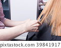 A hairdresser making a haircut for a blonde female 39841917