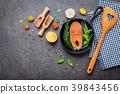 Salmon filet in old cast iron skille on dark stone 39843456