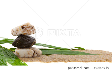 stack of stone and bamboo leaves on sand 39862519
