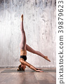 Fit woman doing variation of sirsasana yoga pose 39879623
