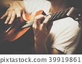 male musician playing classical, acoustic guitar 39919861