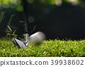Golfer hitting golf ball with club 39938602