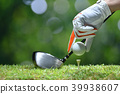 Hand hold golf ball with tee on golf course 39938607