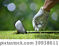 Hand hold golf ball with tee on golf course 39938611