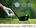 Hand hold golf ball with tee on golf course 39938612