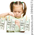 Cute little girl is playing with paper money 39940271