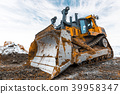 Yellow excavator in career moves overburden. Bulldozer combs the ground, with the bright sun and 39958347