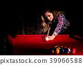 Young woman playing billiards in the dark billiard club 39966588