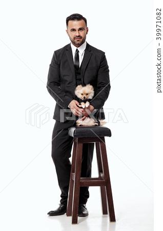 man in black suit holds pomeranian dog 39971082