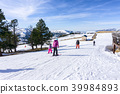 People skiing and snowboarding on a slope  39984893