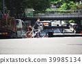 ชายคนหนึ่งกำลังข้ามถนนคนเดินเท้าบนจักรยานถนน 39985134