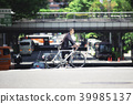 ชายคนหนึ่งกำลังข้ามถนนคนเดินเท้าบนจักรยานถนน 39985137