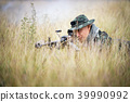 Sniper laying on the grass looking through scope. 39990992