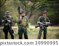 Squad of soldiers patrolling across the forest area. 39990995