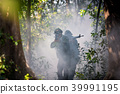 Squad of soldiers patrolling across deep forest. 39991195